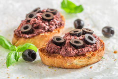 Tasty bruschetta with black olives for a snack Royalty Free Stock Photos