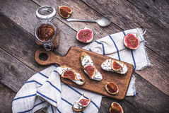 Tasty Bruschetta with jam and figs on napkin in rustic style Stock Photos