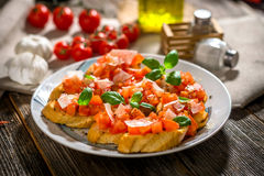 Tasty bruschetta with tomato,  basil, parmesan, olive oil ... Royalty Free Stock Images