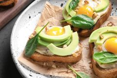 Tasty bruschettas with fried eggs and avocad. O on plate, closeup stock photo