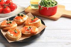 Tasty bruschettas with salmon. On plate Royalty Free Stock Photos