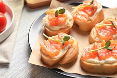 Tasty bruschettas with salmon on plate,. Closeup Royalty Free Stock Images