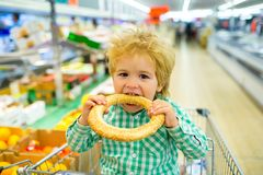 Tasty bun. Boy bites bagel with sesame in the supermarket. Bakery products. Shopping Shopping for food. Child food royalty free stock photo