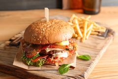 Tasty burger with bacon and french fries. On wooden board Royalty Free Stock Images