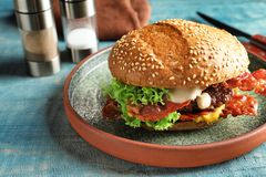 Tasty burger with bacon. On plate royalty free stock image
