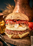 Tasty burger with beef, bacon, fried egg and mushrooms on wooden Stock Image