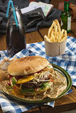 Tasty burger with beef and french fries and soda. Tasty burger with beef and egs and french fries and soda, on a table outdoors Stock Photos