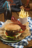 Tasty burger with beef and french fries and soda. On a table outdoors Royalty Free Stock Image