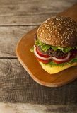 Tasty burger with cheese on wooden table.  stock photo