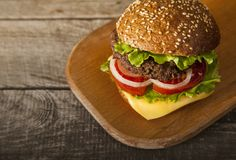 Tasty burger with cheese on wooden table.  royalty free stock photo