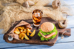 Tasty burger with fish served with cold drink Royalty Free Stock Photography
