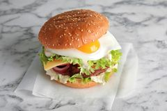 Tasty burger with fried egg. On marble background stock photos