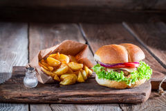 Tasty burger with fries in old wooden board Stock Image