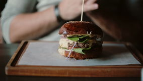 Tasty burger is great on a wooden tray. A man takes his hands and was going to eat. stock video footage