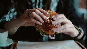 Tasty burger is great on a wooden tray. A woman takes his hands and was going to eat. stock video