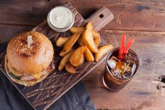 A tasty Burger with snacks in the form of potatoes with white garlic sauce and a glass of cold Cola. juicy Burger with onion rings. Bacon and cheese on a dark Royalty Free Stock Image