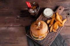 A tasty Burger with snacks in the form of potatoes with white garlic sauce and a glass of cold Cola. juicy Burger with onion rings. Bacon and cheese on a dark Royalty Free Stock Photo