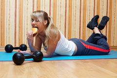 Tasty burger vs fitness training? Royalty Free Stock Photography