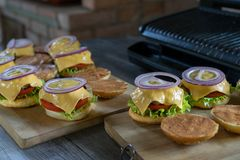 Tasty burgers with cheese, lettuce, onion and tomatoes served outdoor on a wooden table. stock photos