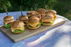 Tasty burgers with cheese, lettuce, onion and tomatoes served outdoor on a wooden table stock images