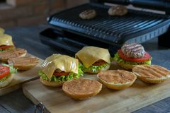 Tasty burgers with cheese, lettuce, onion and tomatoes served outdoor on a wooden table stock image