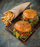 Tasty burgers on wooden table. stock images