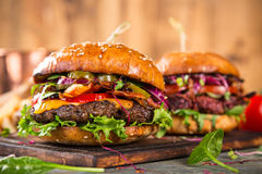 Tasty burgers on wooden table. Stock Photography