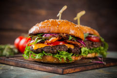 Tasty burgers on wooden table. Royalty Free Stock Photo