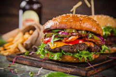 Tasty burgers on wooden table. Royalty Free Stock Photos