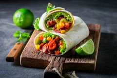 Tasty burrito with spicy salsa and fresh lime stock image