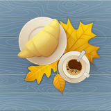 Tasty buttery croissant and cup of hot coffee on old wooden table with autumn leaves. Tasty buttery croissant and cup of hot coffee on old wooden table with Stock Photography