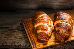 Tasty buttery croissants. On old wooden table Royalty Free Stock Photos