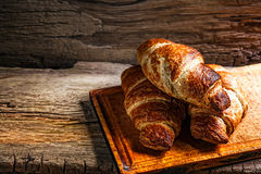 Tasty buttery croissants. On old wooden table Stock Images