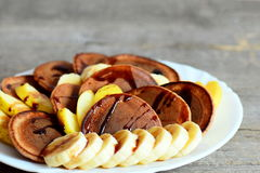 Tasty cacao pancakes. Baked cacao pancakes drizzled with caramel, fresh sliced bananas and apples on a plate Stock Photos