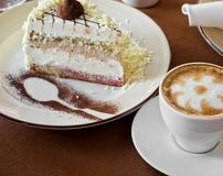 Tasty cake. At plate closeup with coffee cup royalty free stock photo