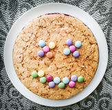 Tasty cake with colorful smarties in funny face shape, festive s Stock Image