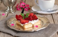 Tasty cake with cream and strawberries. And a cup of tea royalty free stock photo