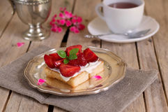 Tasty cake with cream and strawberries. And a cup of tea stock images