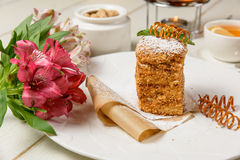 Tasty cake and flowers Stock Images
