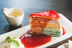 Tasty cake rainbow on wood table , layer cake color and strawberry topping Royalty Free Stock Images