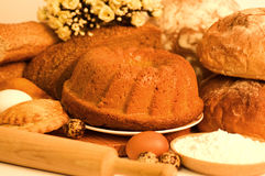 Tasty cakes and bread in basket Stock Photography