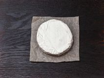 Tasty Camembert cheese. A soft ripened Camembert cheese with a smooth, runny, creamy interior and an edible white rind on a dark wood board stock photography