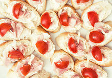 Tasty canapes with butter, ham and cherry tomatoes, food theme Royalty Free Stock Photography