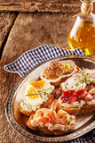 Tasty canapes in a rustic pub or restaurant. On toasted baguette topped with quark cheese and prawns, egg, strawberries, meatballs and radish seasoned with Stock Photography