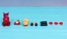 Tasty candies represent in the form of a gummy bear, burger and. Drink that is love on wooden turquoise table Stock Images
