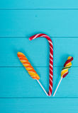 Tasty candy cane and colorful bright lollipops on turquoise boar Royalty Free Stock Photography