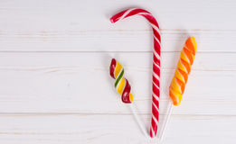 Tasty candy cane and colorful bright lollipops on wooden board Royalty Free Stock Photos