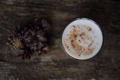 Tasty cappuccino on the table. Coffee with cinnamone on the dark wooden table. Cones near the coffee. Cappuccino.Top view. Place for text Royalty Free Stock Photography