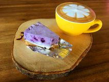 Tasty Capucino art coffee with blue berry cheese cake on wooden place. Close up Tasty Capucino art coffee with blue berry cheese cake on wooden place royalty free stock image