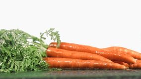 Tasty carrots in super slow motion receiving raindrops stock footage